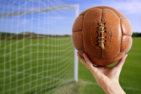 Football vintage ball in hand net soccer goal green grass background photo