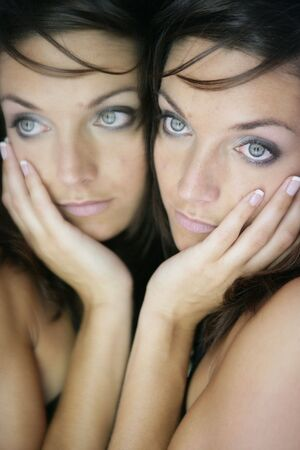 Beautiful blue eyes woman on the mirror as a twins portrait photo