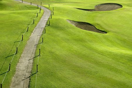 Golf course green grass hill field with holes and track way photo