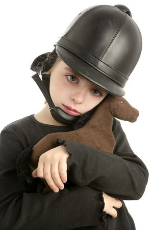Beautiful riding cap little girl hug a toy horse isolated on white photo