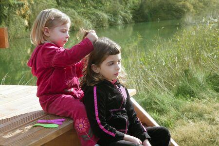 ourdoor: Little sister girls hairdresser on the river ourdoor park Stock Photo