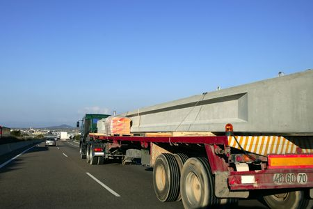 Heavy transportation truck lorry carrying a concrete big beam on a road in Europe photo