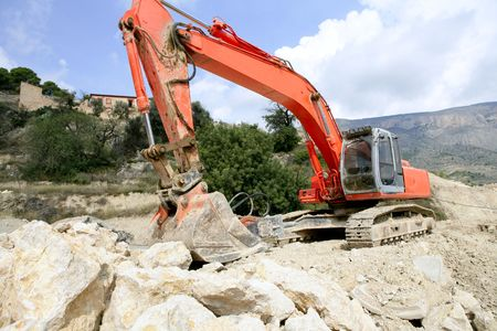 Backhoe bulldozer working hard with stones  photo