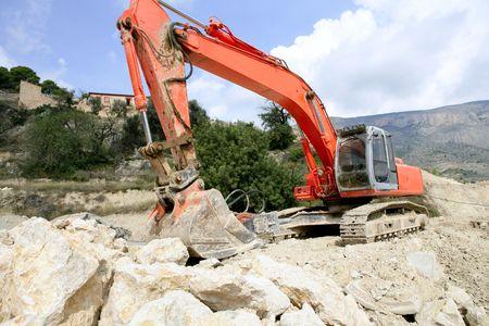 working hard: Backhoe bulldozer working hard with stones  Stock Photo