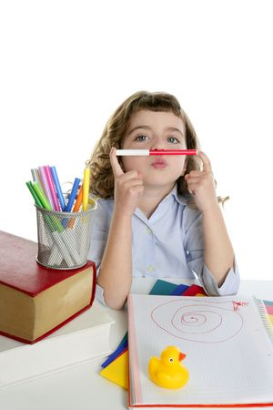 nouse: Brunette student little girl playing with marker on nouse at school desk