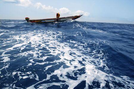 African ethnic boat in atlantic blue water Senegal photo