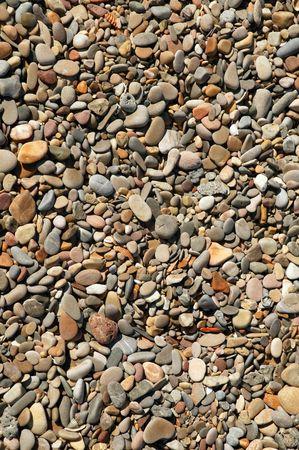 Background texture of little stones from beach sea shore coastline photo