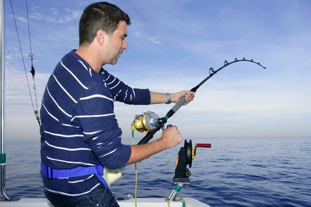 fisherman on boat: Angler fisherman fighting big fish rod and reel saltwater ocean