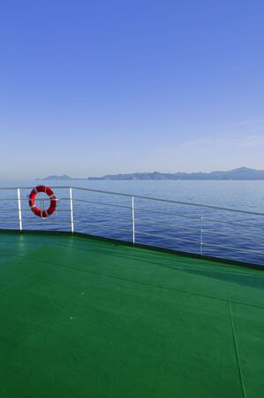 Boat green deck with Ibiza island mountains in background    photo