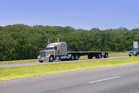 American Truck driving on a road with green forest  photo