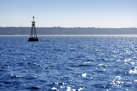 Beacon floating on blue ocean as navigation guide help photo