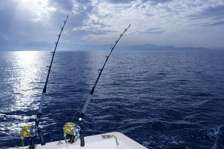 rigger: Fishing boat trolling with two rods and reels on blue ocean Stock Photo