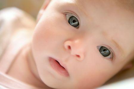 ブロンドの小さな赤ちゃんがベッドの肖像画の水平方向の画像の上に敷設 写真素材