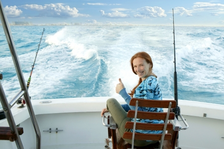 fisherwoman big game on boat chair ok sign happy photo