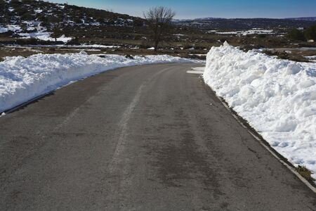 asphalt road curve with snow in both side borders  photo