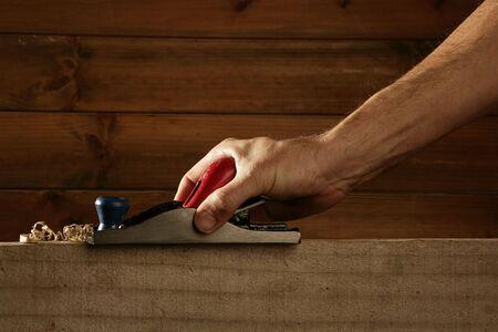 carpenter planning wood planer tool man hand wooden background Stock Photo - 6767535
