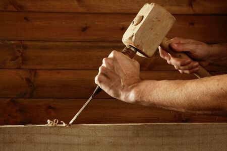 craftman: gouge wood chisel carpenter tool hammer in hand working wooden background Stock Photo