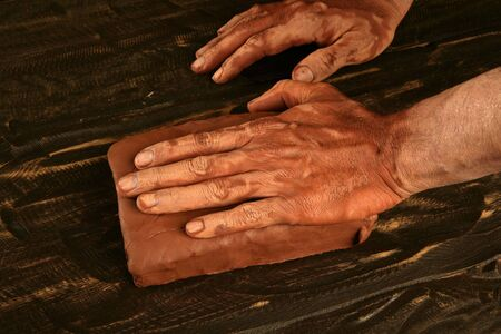red clay: artist man hands working red clay to create handcraft art