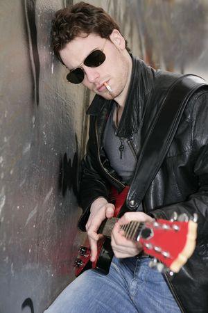 joven fumando: fumar cigarrillos rock cuero chico tocando la guitarra al aire libre sobre fondo de plata de pared