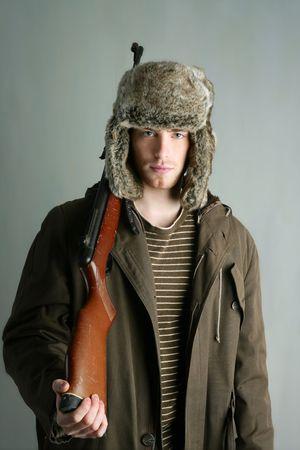 Hunter man fur winter hat holding rifle gun brown autumn coat Stock Photo - 6846621