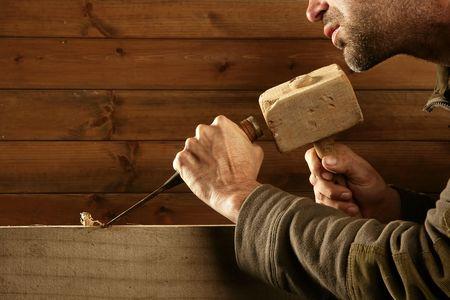 cincel: herramienta de carpintero de cincel de madera de sobrecortes martillo en mano trabajando a fondo de madera