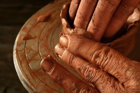 craftmanship: pottery craftmanship red clay potter hands work finger closeup Stock Photo