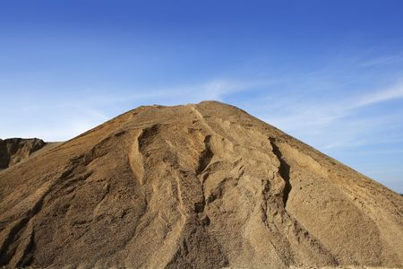 sand quarry: brown construction sand quarry mountain blue sky