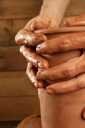 sculptor: pottery craftmanship red clay potter hands work finger closeup Stock Photo