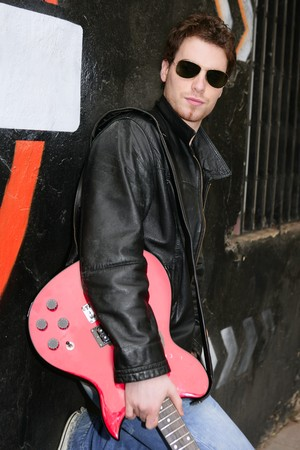 a guitarist boy playing guitar: rocker rock star man on black graffiti holding red electric guitar leather jacket Stock Photo