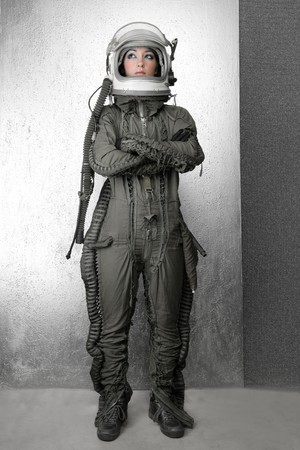 futuristic girl: astronaut fashion woman full length space suit helmet silver studio background