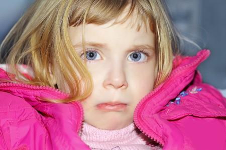 sad gesture blond little girl portrait pink coat photo