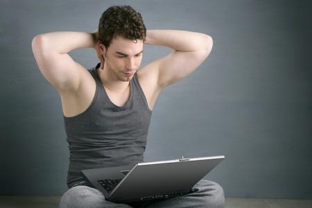handsome student: hombre joven apuesto estudiante sentarse a trabajar en equipo port�til sobre fondo gris