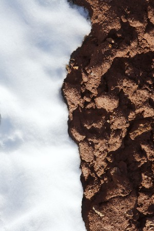 mud and snow: contrast snow and red clay mud soil vertical Stock Photo