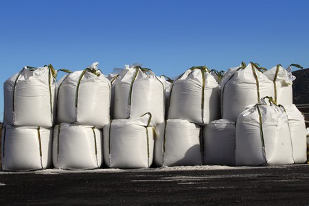 sand quarry: salt big bags sacks stacked rows for iced roads blue sky Stock Photo