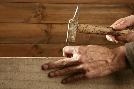 build up: Carpenter hands with hammer wood and nail on wooden background Stock Photo