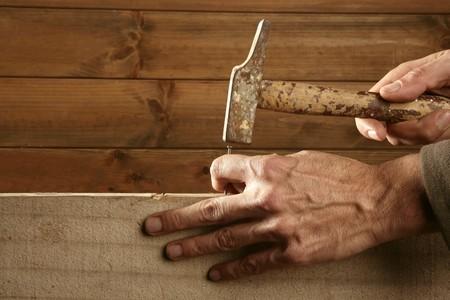 the hammer: Carpenter manos con madera de martillo y clavos sobre fondo de madera