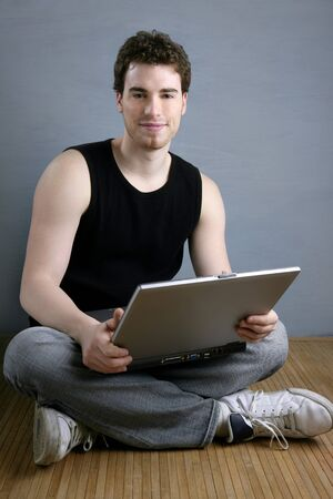 handsome student young man sit working on laptop over gray background photo