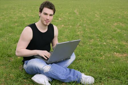student young man laptop computer on green grass meadow outdoor   photo