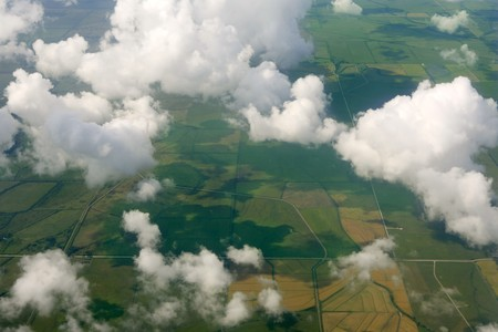 Aircraft bird view of green fields white clouds photo