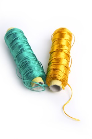 metallic rayon thread line spool in green and golden colors over white  photo
