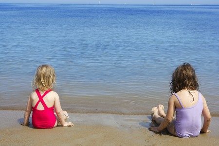 tow sisters sit on beach bathing suit swimsuit back view summer vacation Stock Photo - 7097552