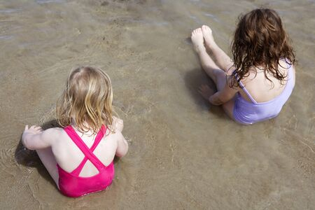 tow sisters sit on beach bathing suit swimsuit back view summer vacation photo