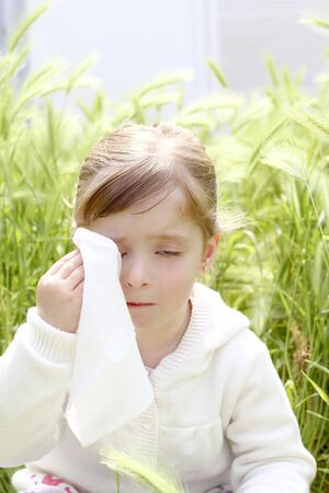 sad little girl crying outdoor green meadow field cereal spike grass photo