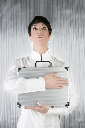 androgynous businesswoman holding silver briefcase over gray background photo