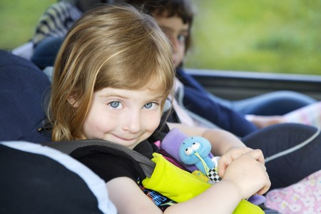 little blonde girl: smiling little girl with safety belt on car security chair Stock Photo