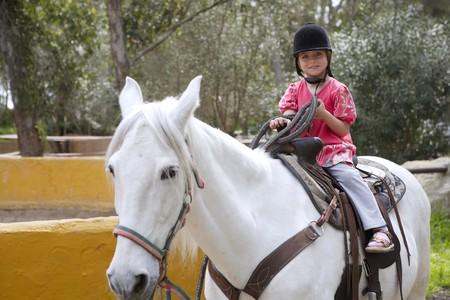 horse saddle: rider little girl jockey hat white horse outdoors park Stock Photo