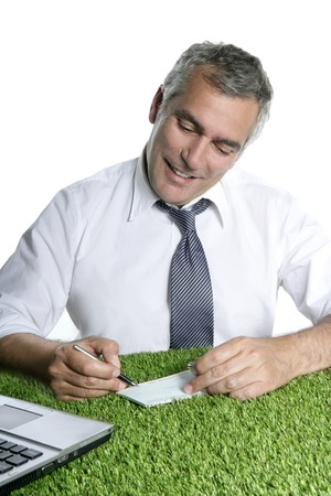 senior businessman signing bank check over green grass desk sport ecology photo