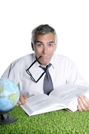 senior student teacher humor glasses world map book green grass ecologycal desk photo