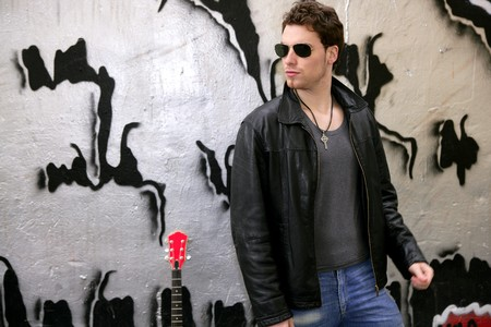 rocker rock star young man sunglasses on silver wall city outdoor photo