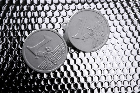 euro two silver coins over bright steel closeup photo